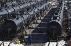 Irving Oil workers inspect rail cars carrying crude oil at the Irving Oil rail yard terminal in Saint John, New Brunswick